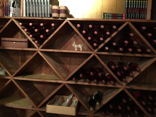 Frankie found a spot on the wine shelves
