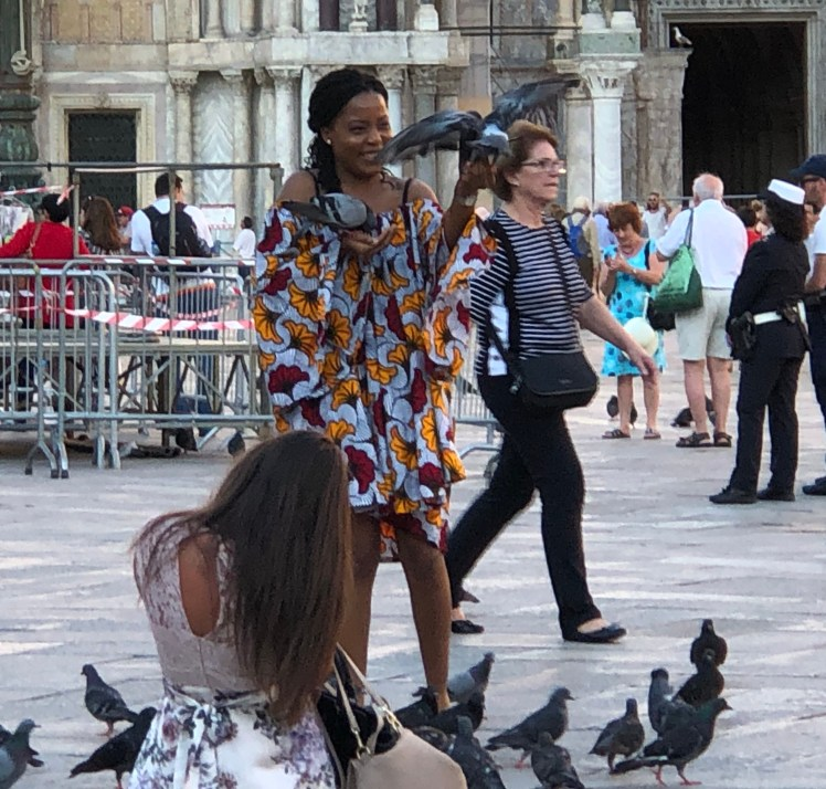 Tourists feeding pigeons at the St. Mark's Square in Venice, La Serenissima