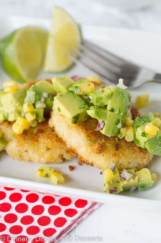Shrimp cakes topped with avocado corn salsa on a plate with  fork