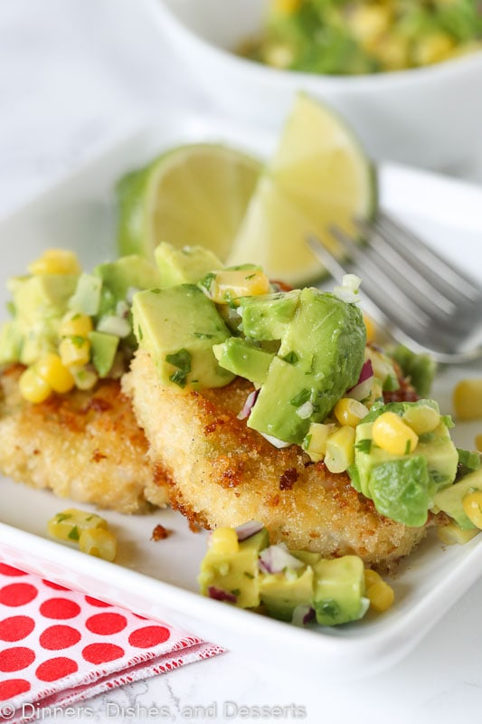 Shrimp cakes topped with avocado corn salsa sitting on a plate