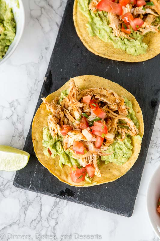 Chicken Tostadas - A quick and easy Mexican dinner! A crispy corn tortilla piled high with guacamole, chicken and salsa. Take a shortcut from the store and this can be ready in no time!