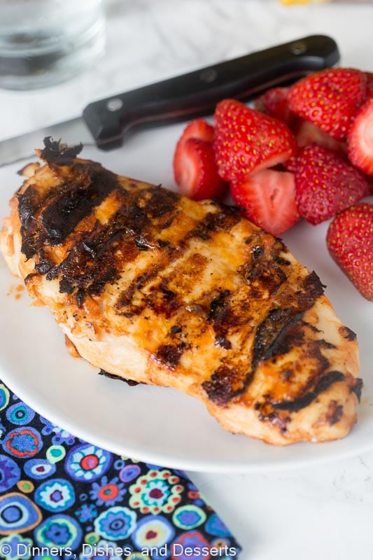 a piece of grilled chicken on a plate next to strawberries
