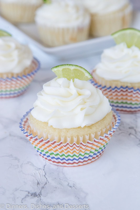 margarita cupcakes topped with frosting and a lime slice
