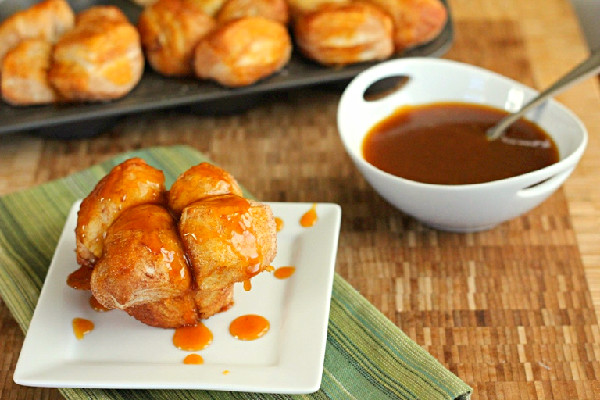 Pumpkin Caramel Monkey Bread Muffins on white plate with bowl of caramel