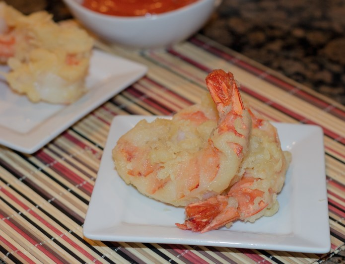 tempura shrimp on white plate with striped napkin