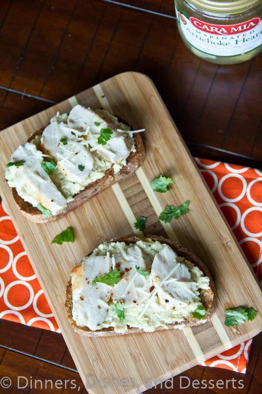 open faced chicken sandwich with artichoke pesto on a board