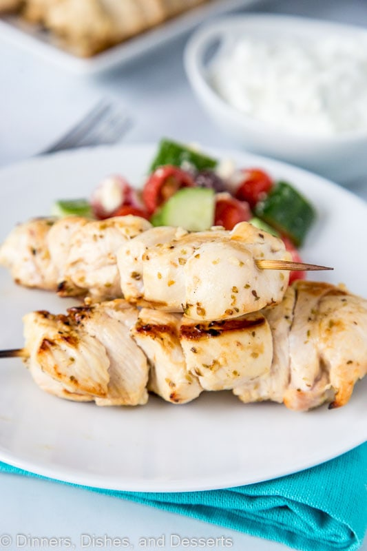 Chicken souvlaki with tzatziki sauce served with greek salad