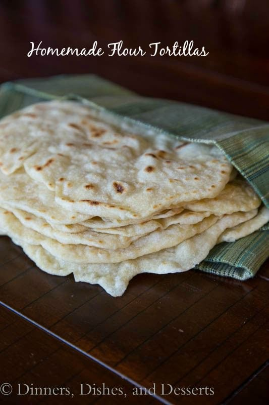 Homemade Flour Tortillas cooked until golden brown and stacked in a towel