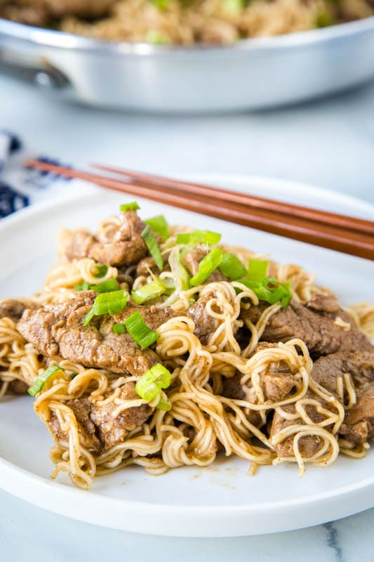white plate with pork lo mein and chop sticks