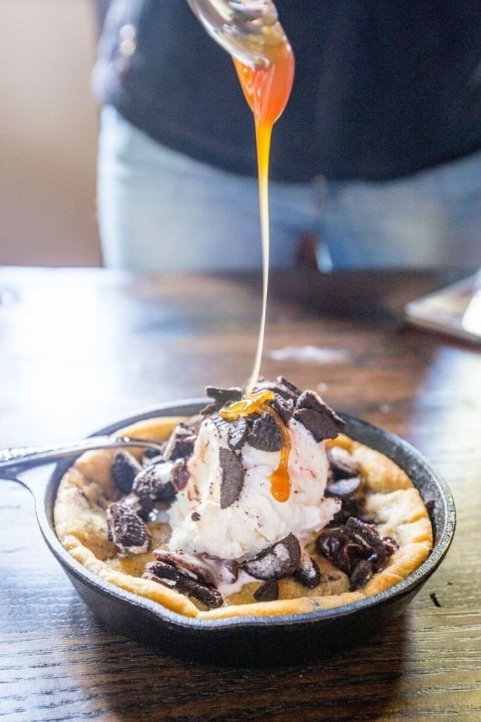 Skillet Cookie - ooey, gooey chocolate chip cookie baked in a skillet, and topped with ice cream, hot fudge, whipped cream and any other toppings your heart desires!