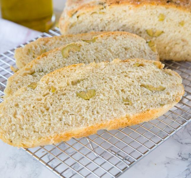 A piece of bread on a plate, with Olive