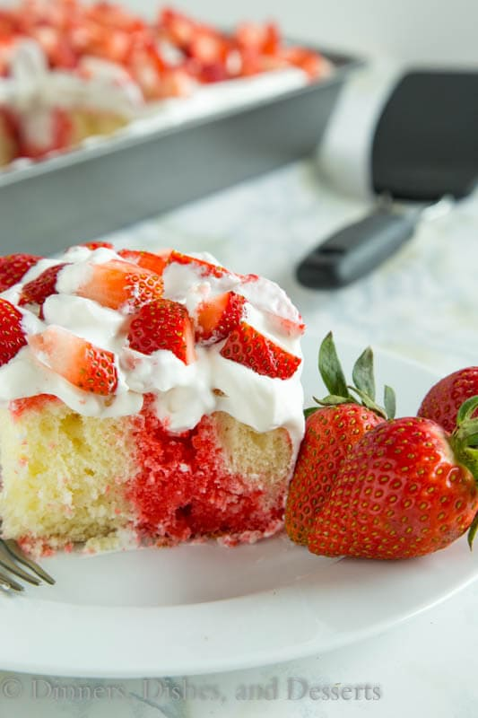 Strawberry poke cake topped with fresh strawberries and fresh whipped cream