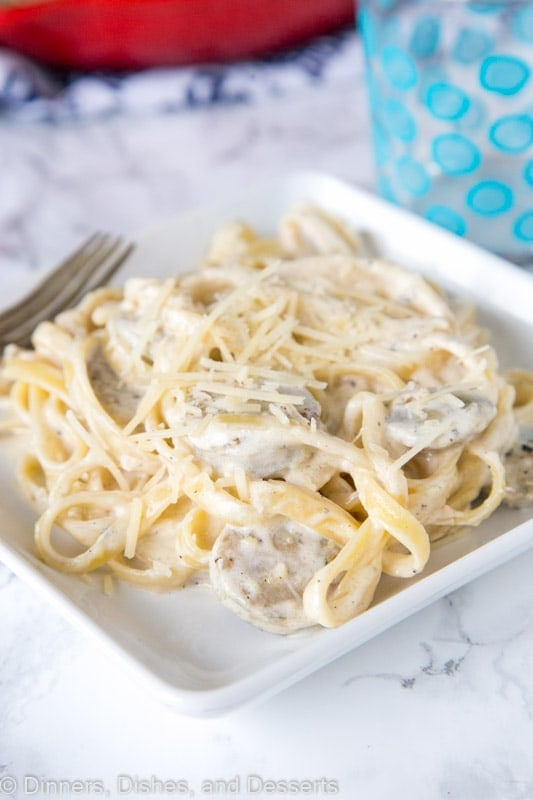 plate of pasta with sauce and cheese, with chicken sausage and Fettuccine Alfredo
