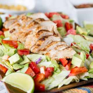 Chicken Fajita Salad - a hearty salad topped with grilled chicken, peppers, onion, avocados, and a salsa vinaigrette dressing. Definitely not your average salad!
