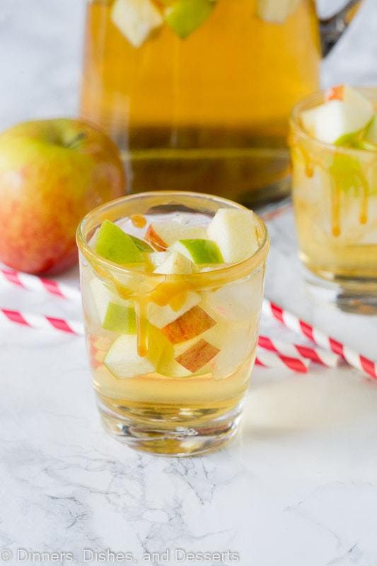 apple sangria in a glass with red and white straws