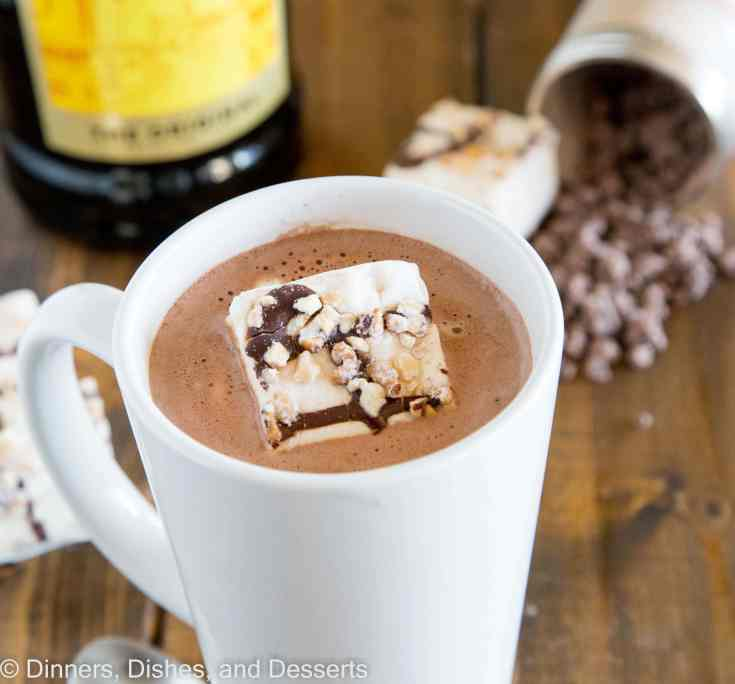 A cup of spiked hot chocolate on a table with marshmallows