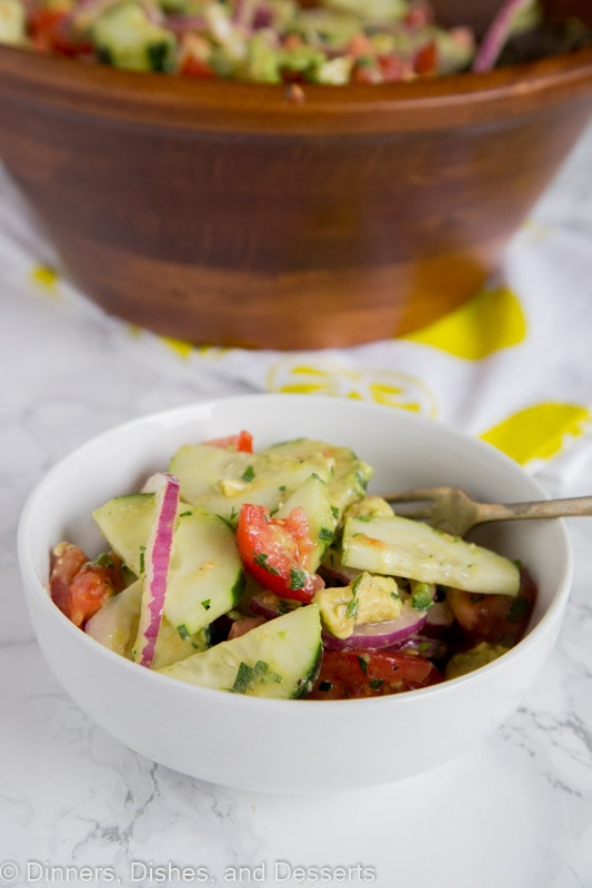 Cucumber Tomato Salad - Easy summer salads are the perfect side dish and great for potlucks. This cucumber salad is full of cucumbers, tomatoes, onions, and avocado tossed with a light vinaigrette dressing.