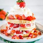 Pancakes layered with whipped cream and strawberries