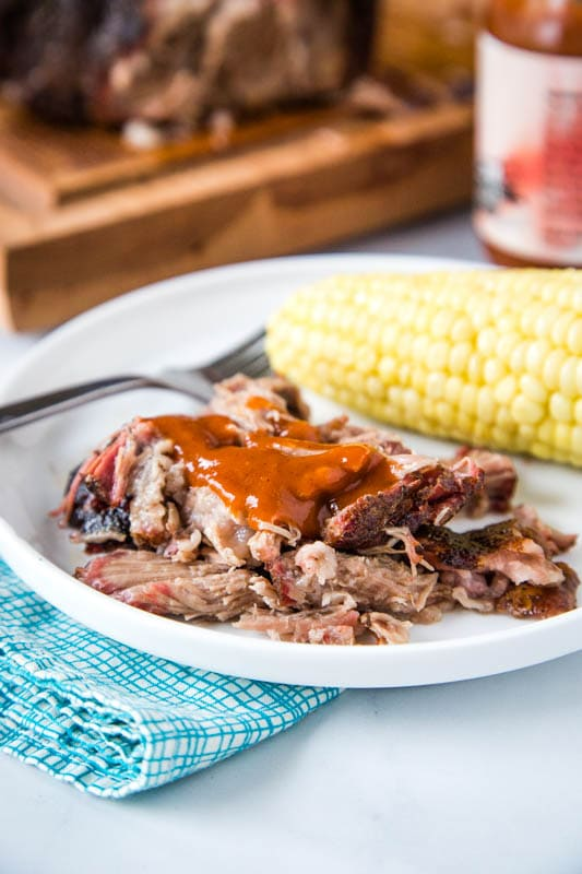 smoked pulled pork with bbq sauce on plate with corn on the cob