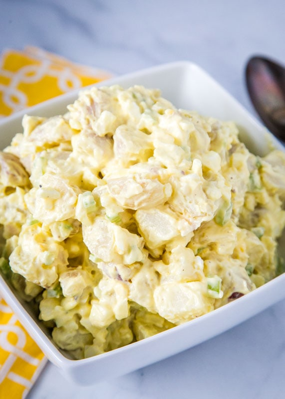 Old fashioned potato salad in white bowl with yellow napkin