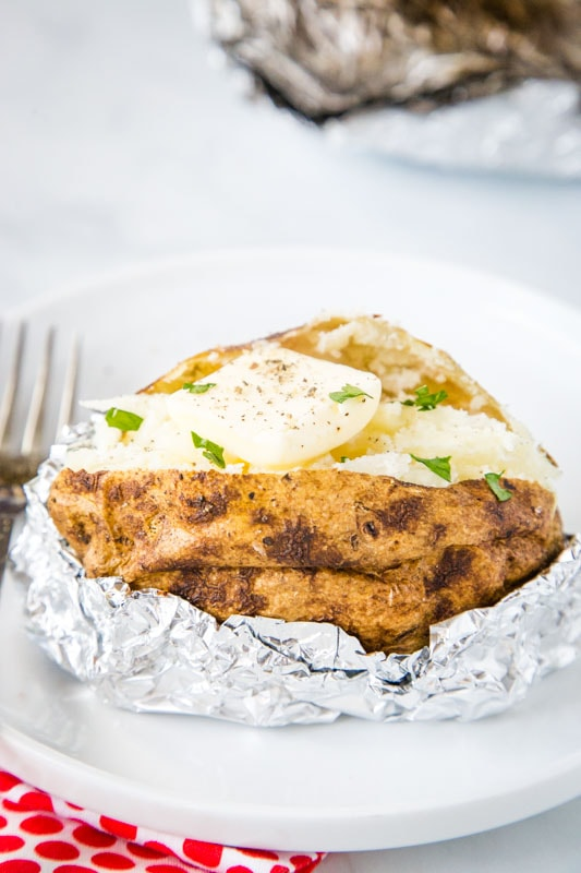 baked potato in foil on white plate cut open with butter
