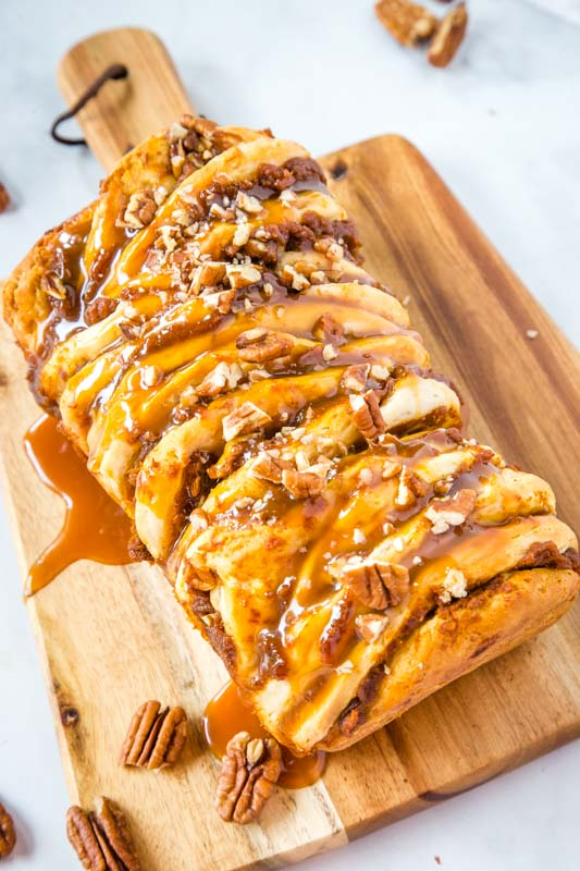 pull apart bread with caramel and pecans on wood cutting board