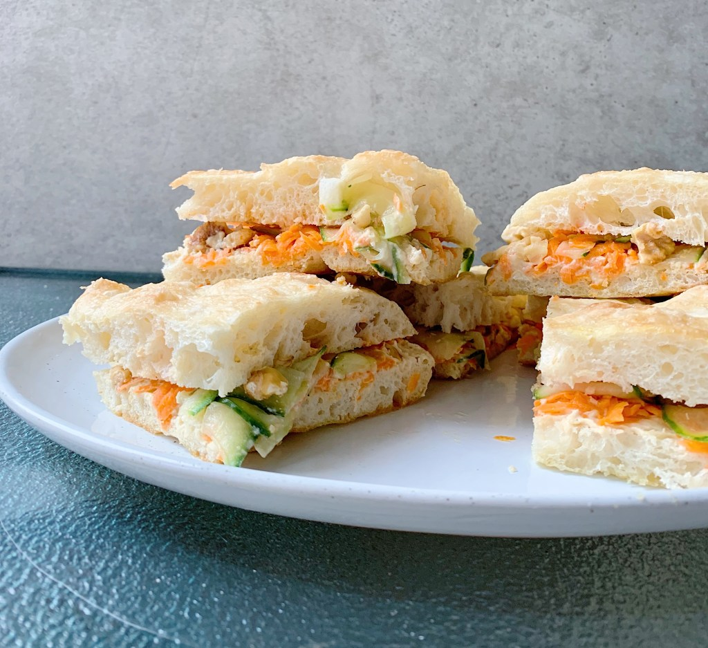 focaccia sandwiches piled, with hummus and carrots for a picnic