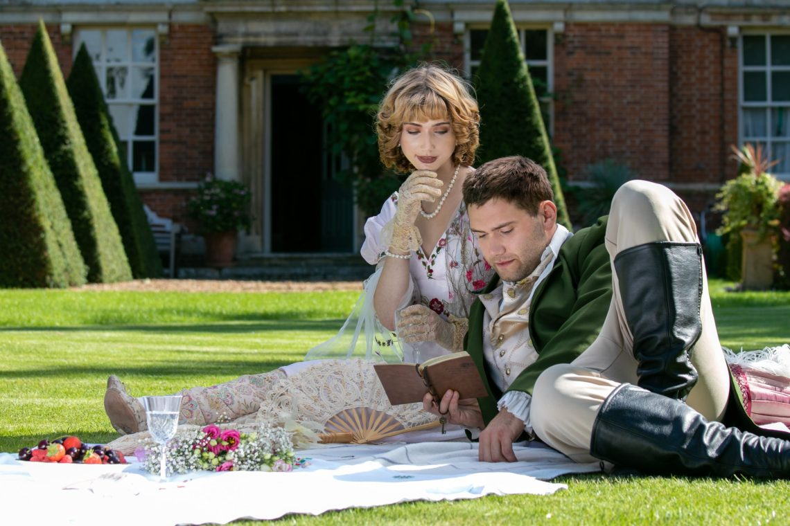 Young lovers dressed in vintage clothing sitting on picnic blanket. Gentleman reading to his lover from a book of poems