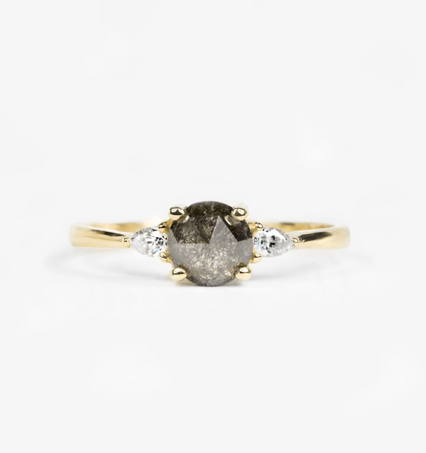 round salt and pepper diamond engagement ring with two pear cut diamonds in yellow gold