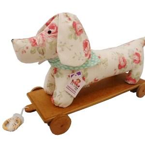 perspectiva de brinquedo educativo, cachorrinho de pano sobre plataforma de madeira com rodinhas