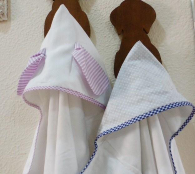 duas toalhas fraldas infantis penduradas, a primeira branca com capuz branco e orelhas lilás, a segunda branca com capuz azul estampado de estrelinhas