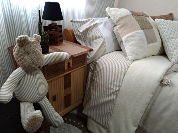 close quarto solteiro com urso de pano sentado em primeiro plano, mesa de cabeceira em madeira com abajour e cactus em segundo plano e cama com lençol, edredom, travesseiro e jogo de almofadas em tons de bege