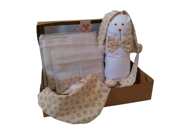 caixa de presente aberta com naninha infantil, babador, paninho de ombro e de boca nas cores branco e rosa