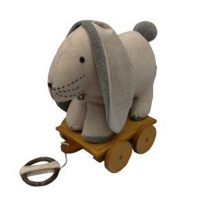 brinquedo infantil coelho de pano bege e cinza sobre base em madeira com rodinhas para criança puxar.