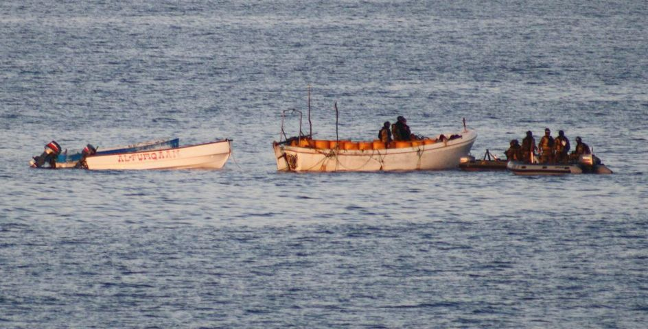 A boarding party from a French warship approaches pirate skiffs off the Somali coast.