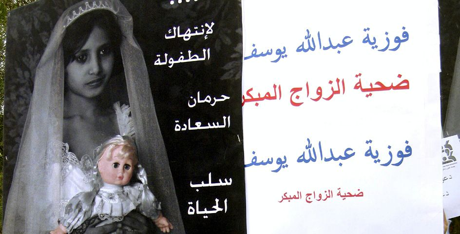 Yemeni school students hold up posters denouncing child marriage outside the parliament in Sana'a, Yemen.