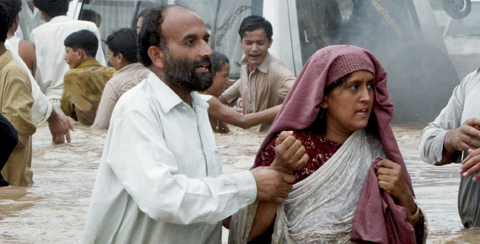 Pakistani villagers move to a safe place from a flooded village near Nowshera, Pakistan.