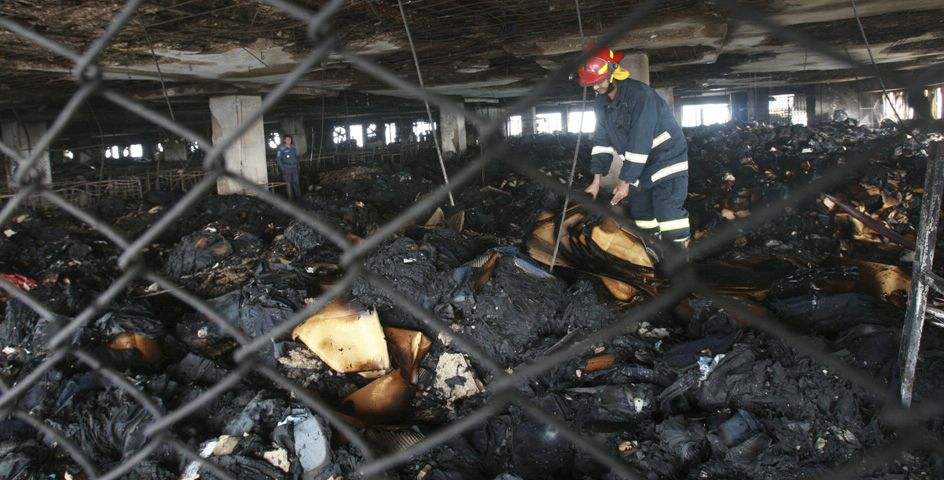 A fireman searches inside a garment factory that was gutted by fire in Ashulia, Bangladesh.