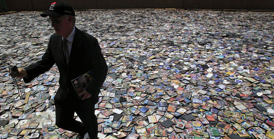 A man walks across thousands of pirated books, CDs, and DVDs seized in Lima, Peru. © AP Image