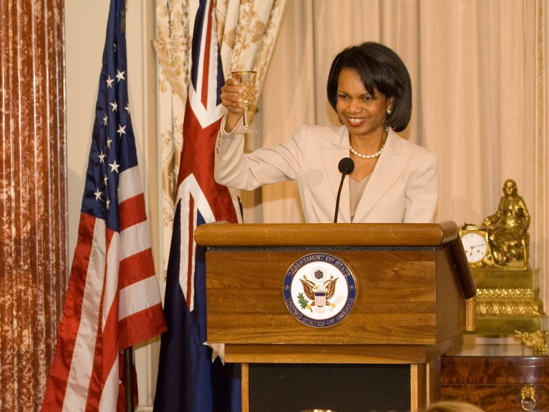 Secretary of State Condoleezza Rice raises a glass from the podium in honor of Australian Prime Minister John Howard, who can be seen sitting at lower left, during his visit to the State Department in Washington, Monday May 15, 2006.
