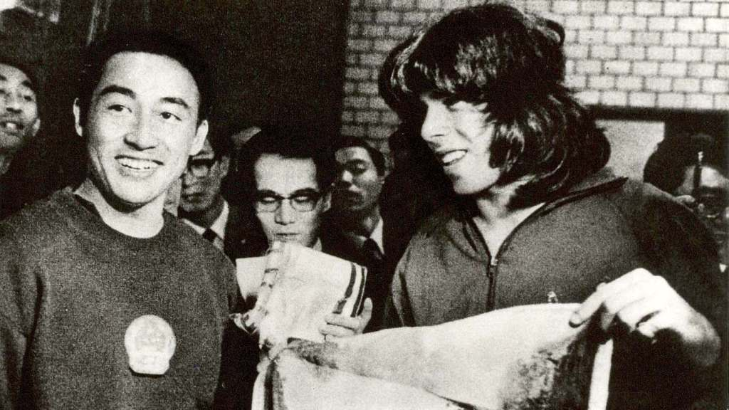 Chinese three-time world champion Ping Pong player Zhuang Zedong (left) presented a Yellow Mountain silk weaving art piece to American athlete Glenn Cowan (right) on Apr 4, 1971. Photo credit: Xinhua News Agency.