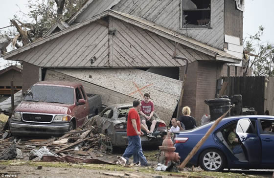A boy sits on the trunk of a car outside a house which has been wrecked in the storm. Credit: Reuters