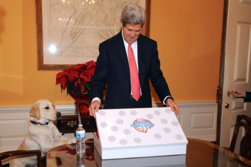 Celebrating Secretary Kerry's 70th Birthday With Cookies In honor of his 70th birthday, U.S. Secretary of State John Kerry, accompanied by his dog Ben, receives a box of Kilvert and Forbes Bakeshop cookies from his staff at the U.S. Department of State in Washington, D.C., on December 11, 2013. In 1976, the Secretary, a chocolate lover, and his friend and business partner K. Dunn Gifford founded the Boston bakery and named it after their mothers. Though the Secretary is no longer at Kilvert and Forbes, he still loves chocolate. [State Department photo/ Public Domain]