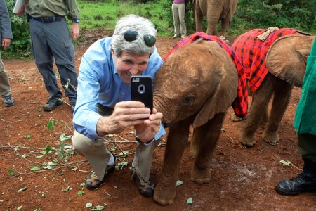 Secretary Kerry Poses for a Photo with a Baby Elephant at the Sheldrick Elephant Orphanage  U.S. Secretary of State John Kerry poses for a photo with a baby elephant at the Sheldrick Elephant Orphanage in Nairobi National Park in Nairobi, Kenya, on May 3, 2015, following a wildlife tour of the Park and before a series of government meetings. [State Department Photo/Public Domain]