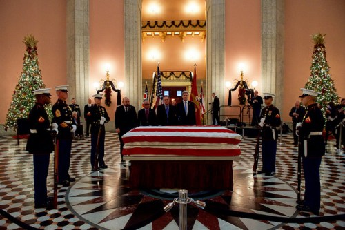 U.S. Secretary of State John Kerry, joined by NASA Administrator Charles Bolden, Ohio House Speaker Cliff Rosenberger, and Ohio Governor John Kasich, pays his respects as the body of astronaut John Glenn, the Secretary's friend and former U.S. Senate colleague, lies in repose in the Ohio Statehouse in Columbus, Ohio, on December 16, 2016. [State Department photo/ Public Domain]
