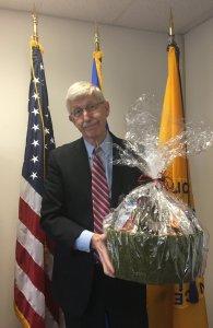 Dr. Collins holding a fruit basket.