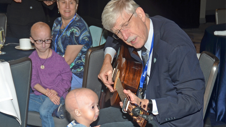 Dr. Collins playing a guitar with children looking on.