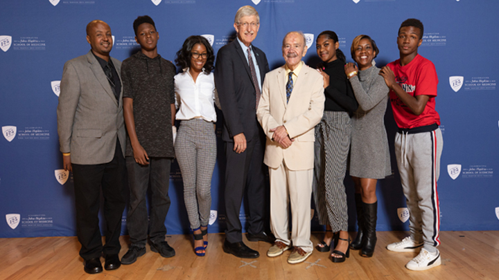 Francis Collins standing with Roland Pattillo and Lacks family members