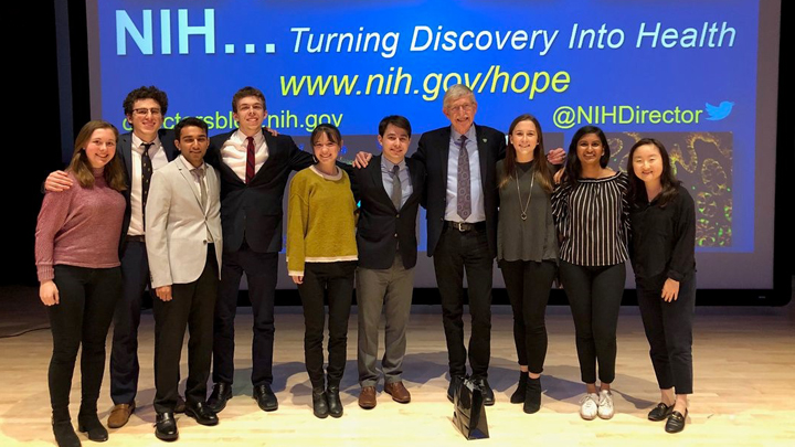 Dr. Francis Collins poses with students on stage at Johns Hopkins University