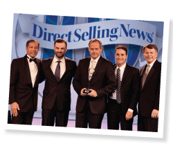 Carlucci (center) and other team members are presented with an award in honor of Natura's ranking at No. 5 on the DSN Global 100.